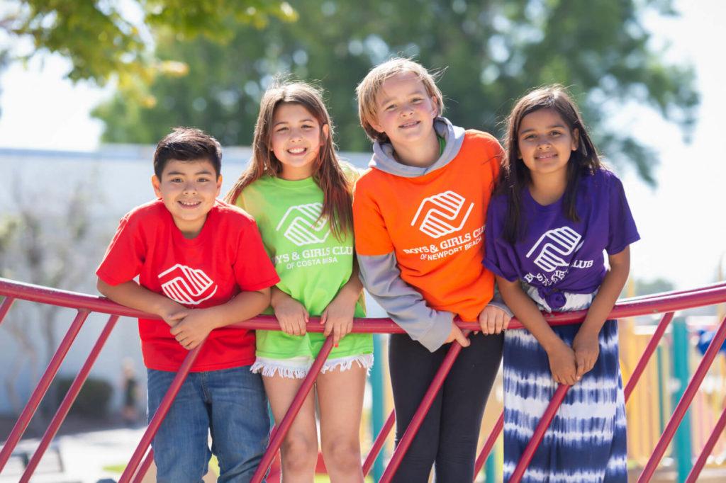 4 children smiling on playground bridge