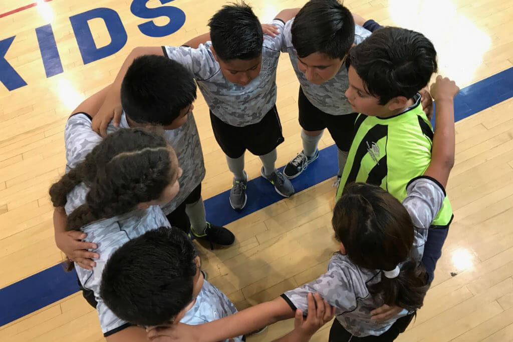 basketball team huddling on court