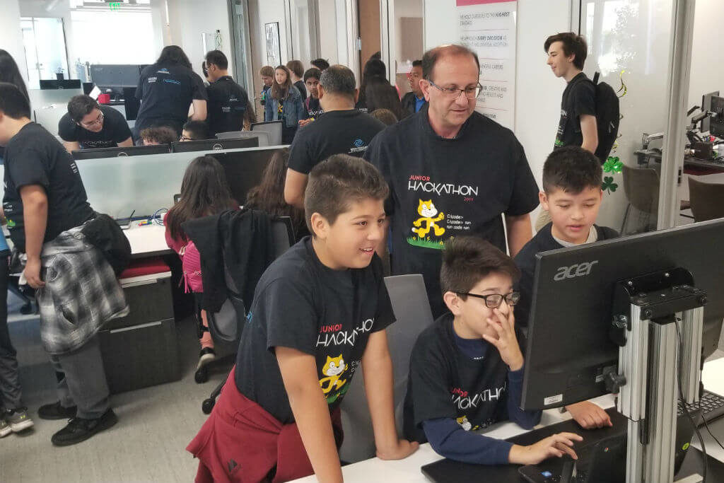 teachers helping children on computers
