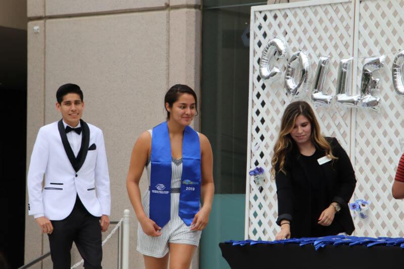 female graduate walking across stage, male graduate behind her